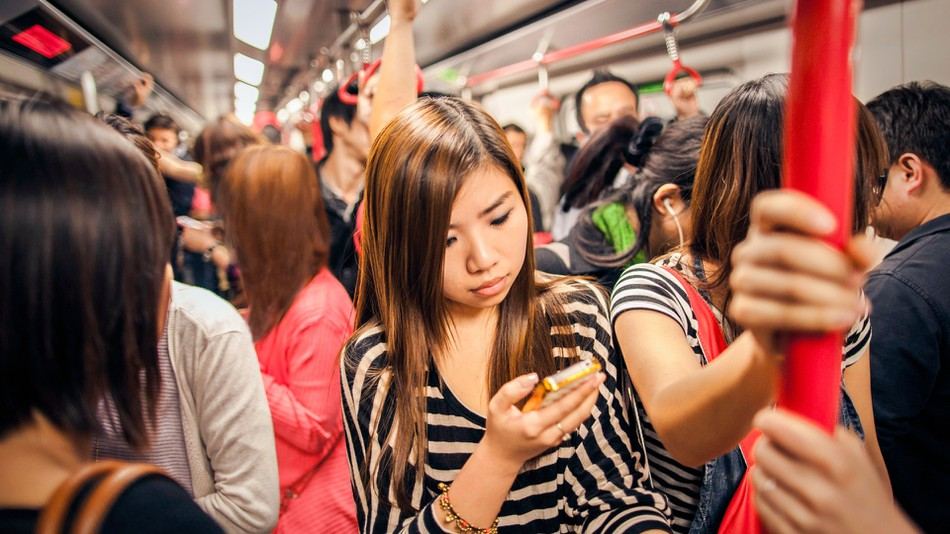 woman on subway watching video captions on her phone